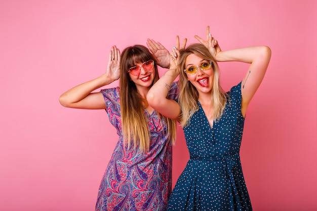 親友のクーペ。バニーの耳を自分の手で真似、カラフルな夏のドレスとサングラスを身に着け、ピンクの壁、パーティータイム。 無料写真