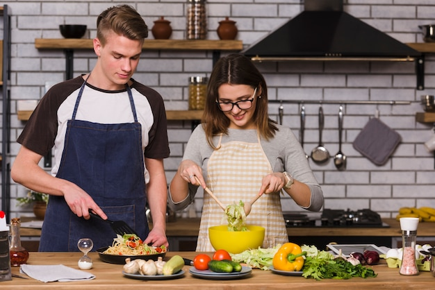 Couple in aprons cooking food in kitchen Free Photo