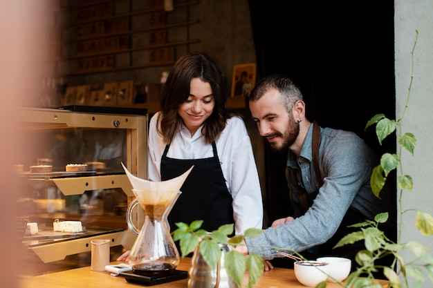 Couple in aprons looking at coffee filter Free Photo