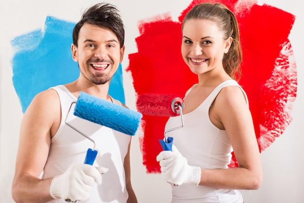 Пары делают ремонт дома и красят стену. Premium Фотографии