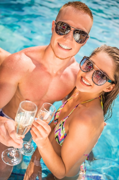 Couple are drinking champagne while having fun in pool. Premium Photo