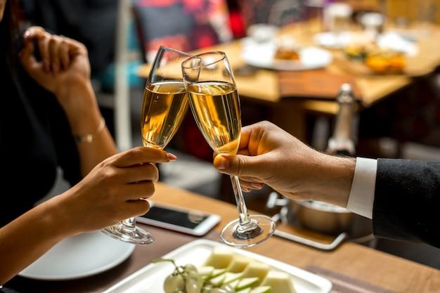 Пара держат бокалы с шампанским с фруктами, вид сбоку Бесплатные Фотографии
