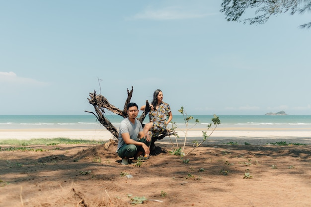 Couple are sitting together in on the beach under the tree pine. Premium Photo