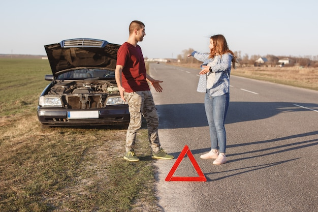Couple argue on road, have problem with broken car, being in panic, don`t know what to do, red warning triangle warns other drivers about damage. husband and wife sort out relationship near auto Premium Photo