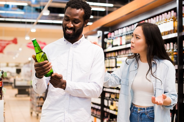 Couple arguing about beer at grocery store Free Photo