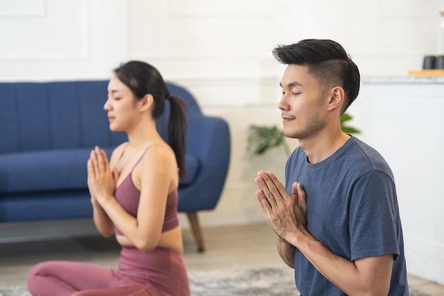 Premium Photo | Couple asian both man and woman practicing yoga and  meditating at home