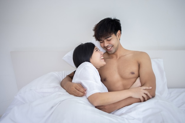 Couple asian man and woman on bed in white bedroom Premium Photo