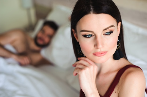 Couple in bed, portrait of a sad woman in bed with her husband Premium Photo