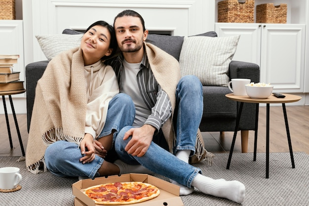 Couple in blanket watching tv and eating pizza Free Photo