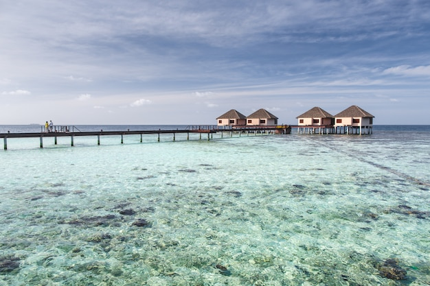 Couple on bridge to water villas on crystal clear water at tropical island Premium Photo
