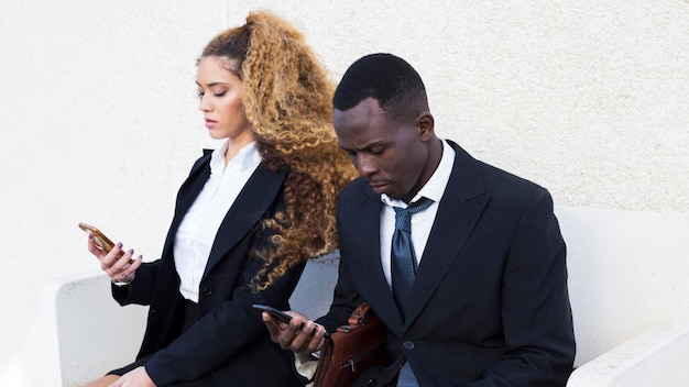 Couple of business people looking at smartphone on bench Free Photo