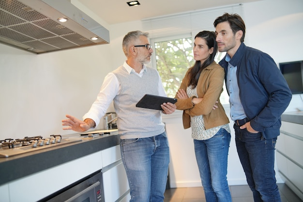 Couple buying new contemporary kitchen in showroom Premium Photo