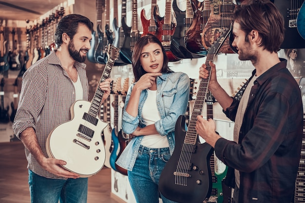 Couple buying new electric guitar in music store. Premium Photo