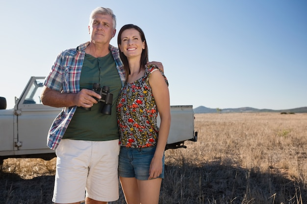 Couple by vehicle on landscape Free Photo