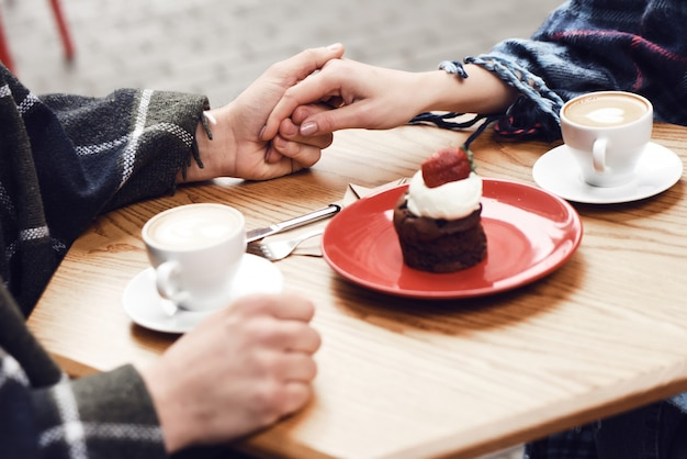Couple in cafe holding hands strawberry cupcake. Premium Photo