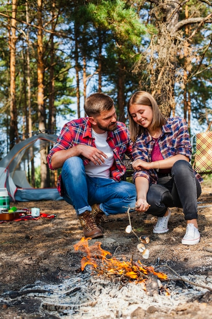 Couple at camping cooking marshmellow on fire Free Photo