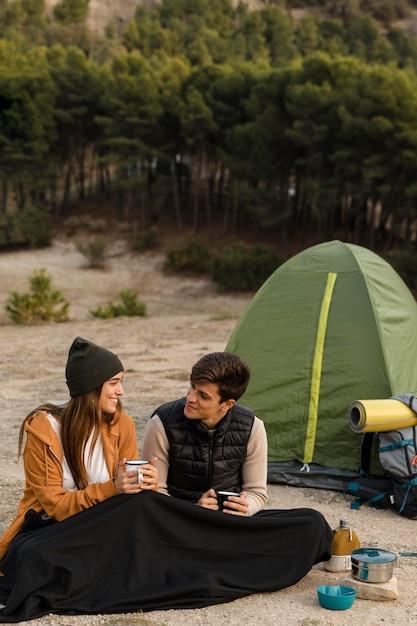 Coppia in campeggio nel campo lungo della foresta Foto Gratuite