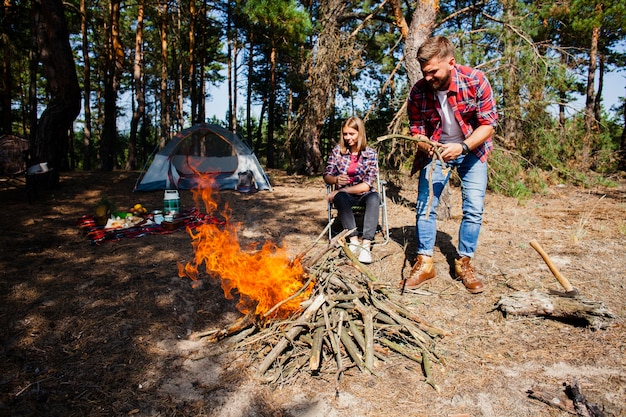Couple camping making fire in woods Free Photo