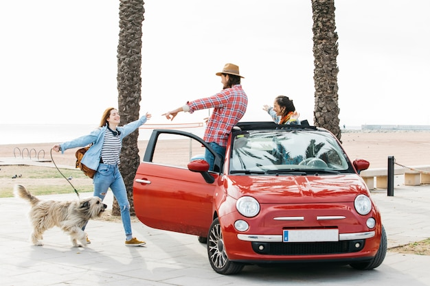 Couple in car greeting woman with dog outdoors Free Photo
