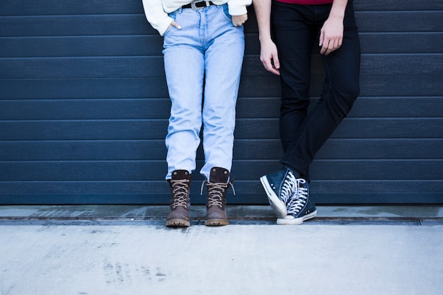 Couple in casual clothes standing against blue wall Free Photo