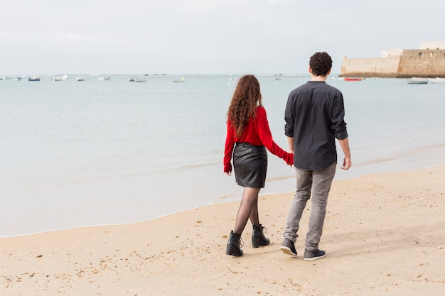 Couple in casual clothes walking on sea shore Free Photo