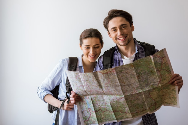 Couple in casual clothes and with backpacks holding a map. Premium Photo