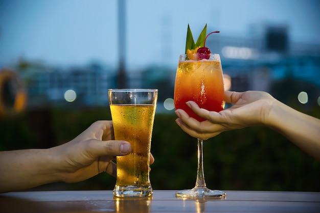 Празднование пары в ресторане с безалкогольным пивом и май тай или май тай Бесплатные Фотографии
