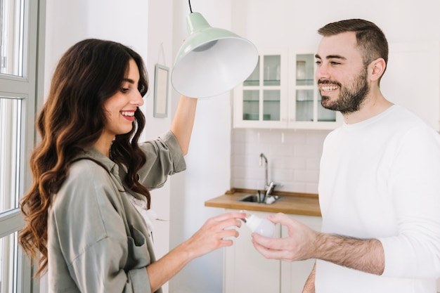 Couple changing bulb at home Free Photo