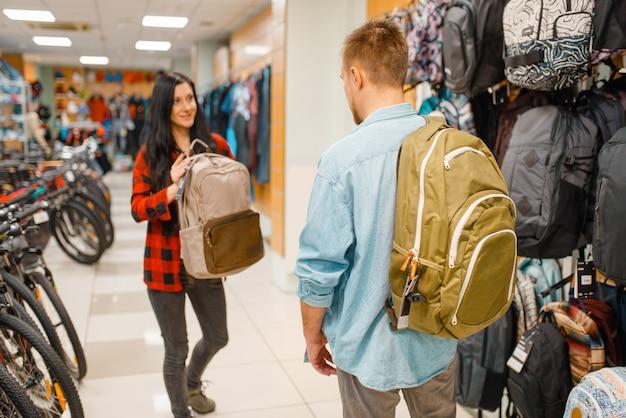 Пара, выбирая рюкзаки для путешествий, покупок в спортивном магазине. Premium Фотографии