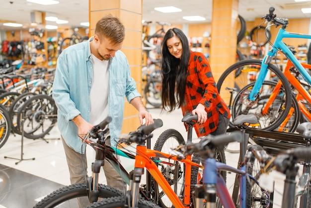 Пара, выбирая велосипеды, делая покупки в спортивном магазине. Premium Фотографии
