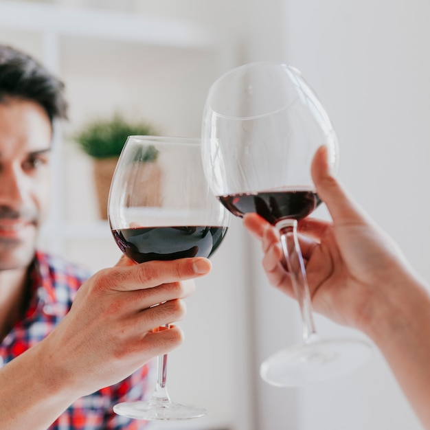 Couple clinking glasses of red wine Free Photo