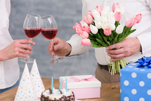 Couple clinking wine glasses with tulip flowers bouquet; birthday cake and gift boxes on table Free Photo