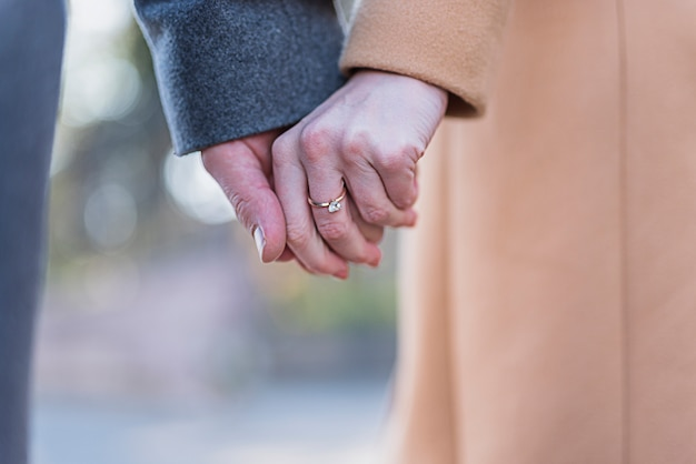 Couple in coats holding hands Free Photo