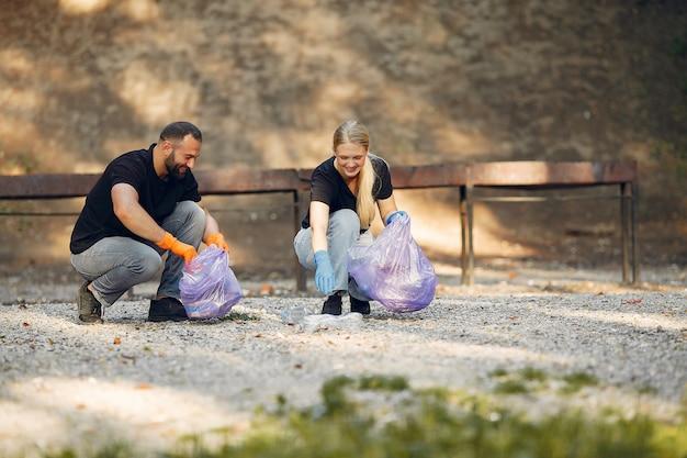 La coppia raccoglie l'immondizia nei sacchetti di immondizia in parco Foto Gratuite