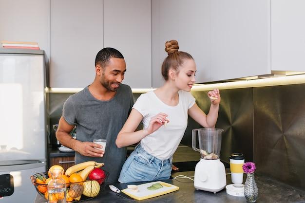 Coppie che cucinano insieme nell'accogliente cucina. la ragazza mette la frutta in un frullatore, la bionda ama una dieta sana. la coppia trascorre del tempo nella casa moderna. Foto Gratuite