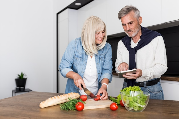Couple cooking together in kitchen Free Photo