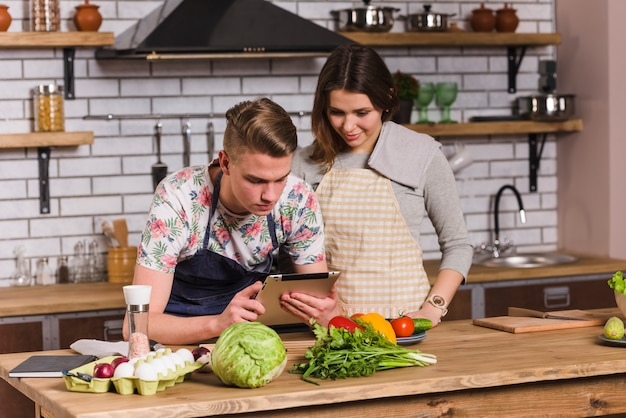Couple cooking and using tablet in kitchen Free Photo