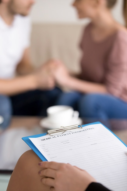 Couple counselling. female psychotherapist with clipboard and happy reconciled family Free Photo