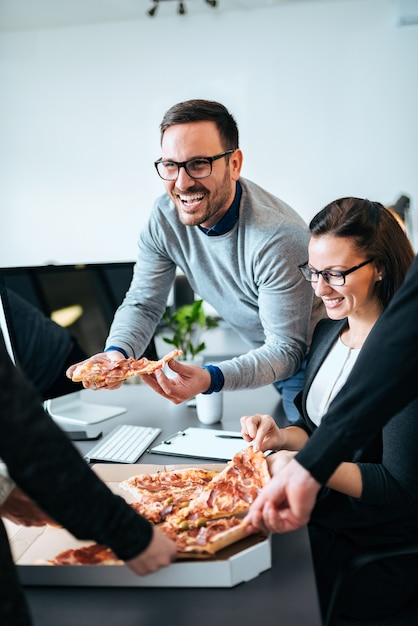Couple of coworkers having lunch break, eating pizza. Premium Photo
