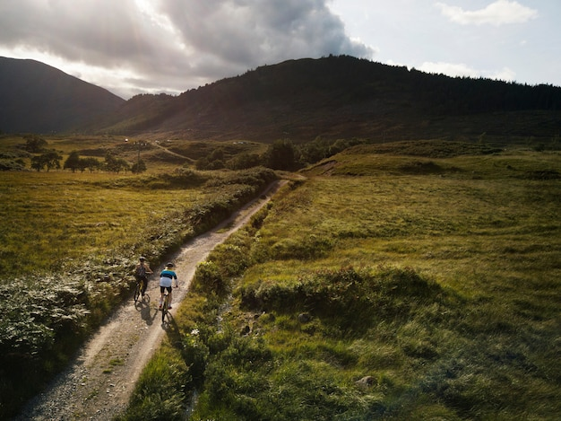 Couple cycling down a road in the scottish highlands Premium Photo