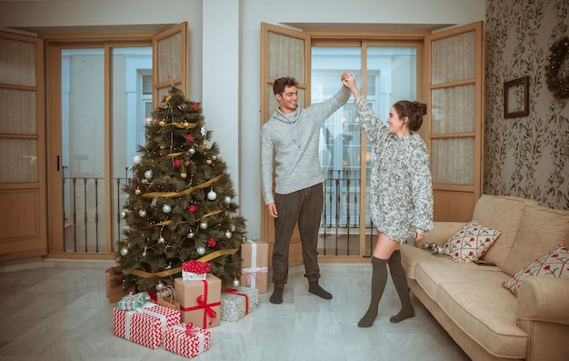 Couple dancing in living room decorated for christmas Free Photo