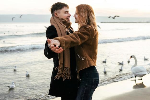 冬のビーチで踊るカップル 無料写真