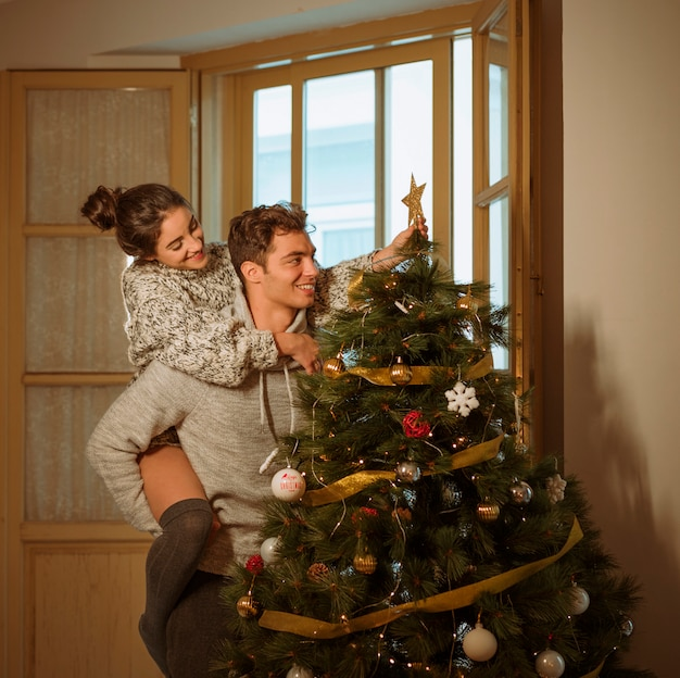 Couple decorating christmas tree with star Free Photo