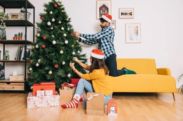 Couple decorating christmas tree Free Photo