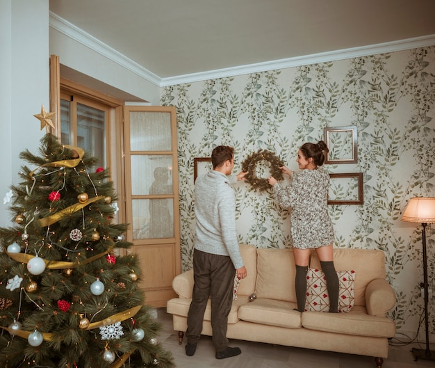 Couple decorating room for christmas Free Photo