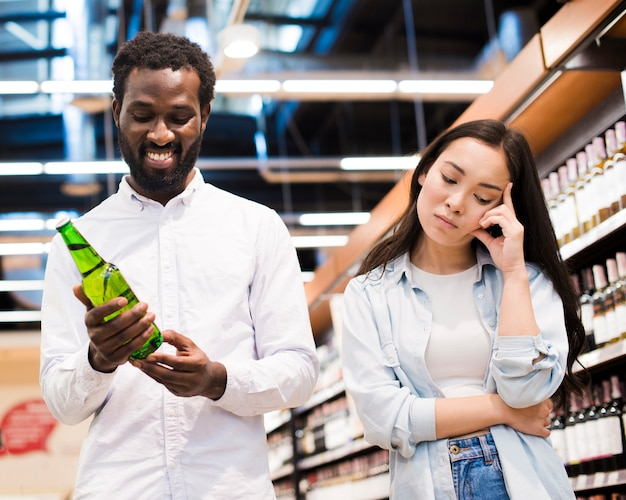 Couple disagreeing about beer at grocery store Free Photo