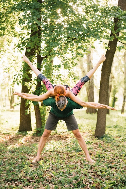 Couple doing balance practicing yoga in park Free Photo