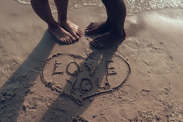 Couple draws picture of heart with 'love you' sign on sand Premium Photo