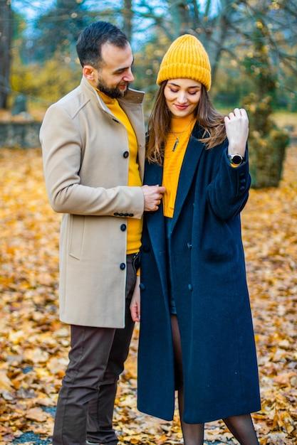 秋の公園で黄色いタートルネックと黄色い帽子に身を包んだカップル Premium写真