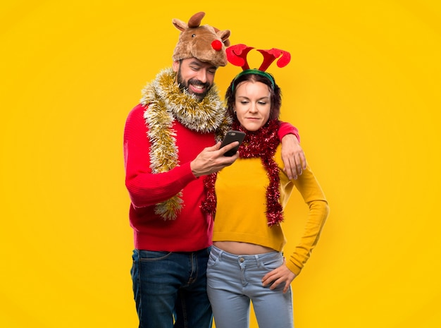 Couple dressed up for the christmas holidays holding a mobile on yellow background Premium Photo